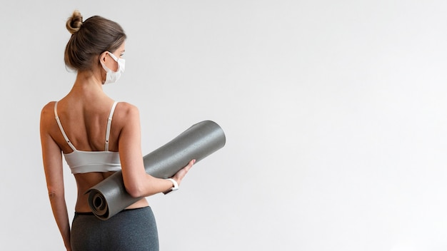 Вид сзади женщины с медицинской маской, держащей коврик для йоги Бесплатные Фотографии