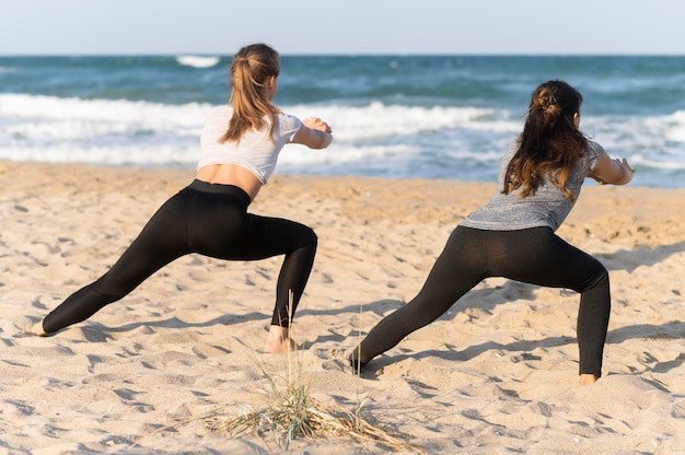 Вид сзади женщин, тренирующихся на пляже Бесплатные Фотографии