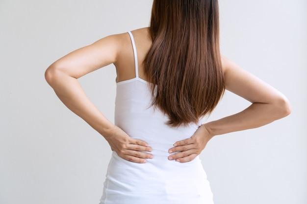 白い背景で隔離腰痛に苦しんでいる若いアジアの女性の背面図。閉じる Premium写真