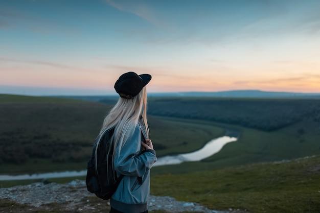 Вид сзади молодой блондинки с рюкзаком, наслаждаясь закатом на пике холмов. концепция путешествия. Premium Фотографии