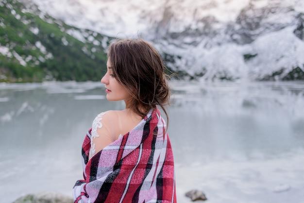 Вид сзади молодая брюнетка девушка в горах зимой возле замерзшего озера Бесплатные Фотографии