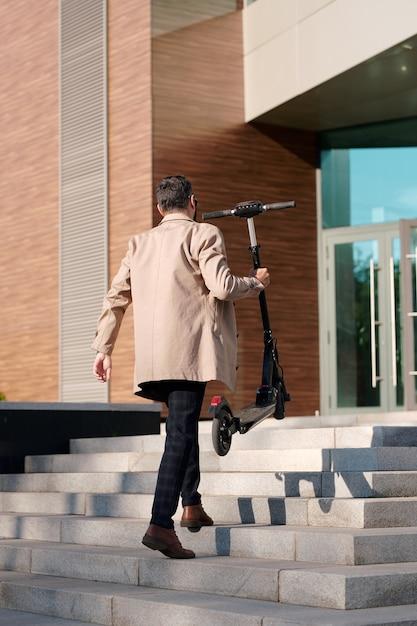 사무실 센터에 들어가기 위해 위층으로 이동하는 동안 전기 스쿠터를 들고 스마트 Casualwear에서 젊은 우아한 사업가의 다시보기 프리미엄 사진
