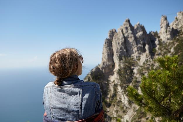 Вид сзади молодой женщины в джинсовой куртке и солнцезащитных очках, стоящей на вершине горы, любуясь великолепным морским пейзажем и панорамным видом на скалы ай-петри во время путешествия в одиночестве. крымская природа. Бесплатные Фотографии