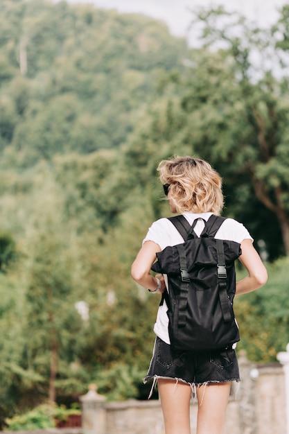晴れた良い日、旅行、冒険、道路、リラックス、休日に山を旅行バックパックと短い髪型の若いきれいな女性の背面図 無料写真