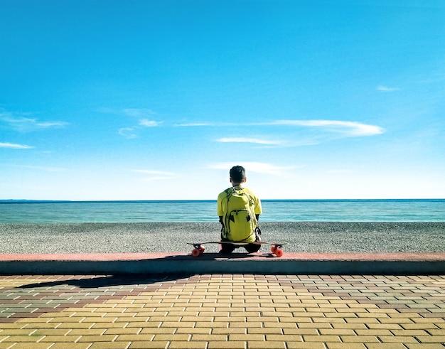 Вид сзади молодого фигуриста, сидящего и расслабляющегося на лонгборде или скейтборде на пляже в море и фоне голубого неба Premium Фотографии