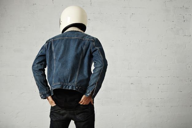 Younf 모터 사이클리스트의 몸에 맞는 뒷모습은 헬멧, 검은 색 긴 소매 헨리 셔츠 및 클럽 데님 재킷을 착용하고 바지 뒷주머니에 손을 넣습니다. 무료 사진