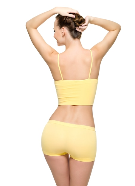 Back view of a perfect female body with thin waist posing isolated on white wall Free Photo