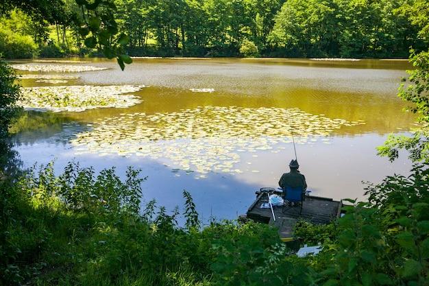 Vista posteriore di una persona di pesca al colpo in un lago nel wiltshire, regno unito nelle prime ore del mattino Foto Gratuite