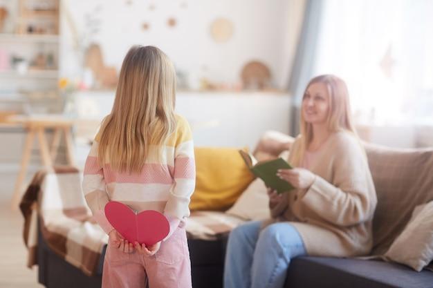 居心地の良い家のインテリア、コピースペースで母の日に彼女を驚かせながらお母さんのための手作りカードを保持しているかわいい女の子の背面図の肖像画 Premium写真