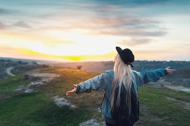 Вид сзади портрет молодой счастливой белокурой девушки с черным рюкзаком и кепкой, держась за руки как самолет на пике холмов на закате. концепция путешествия. Premium Фотографии