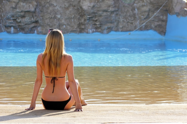 Back view portrait of a single woman watching on a water pool Premium Photo