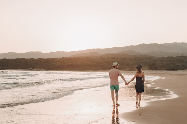 Back view of a romantic hipster couple walking at beach during summer vacation at sunset Free Photo