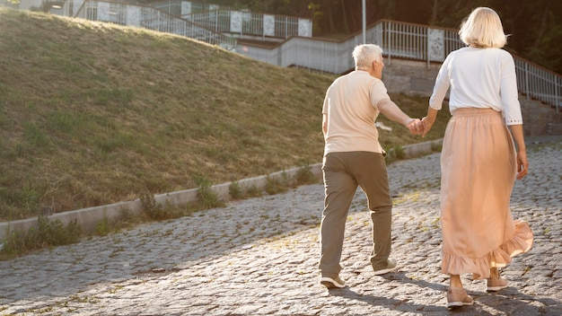 Back view of senior couple holding hands while out in the city Free Photo