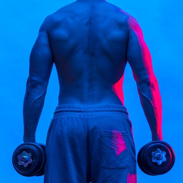 Vista posteriore dell'uomo in forma senza camicia che tiene i pesi Foto Gratuite