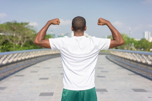 Back view of sporty black guy posing and flexing both biceps. Free Photo