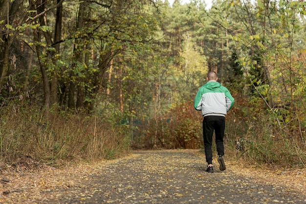 Back view sporty man jogging in nature Free Photo