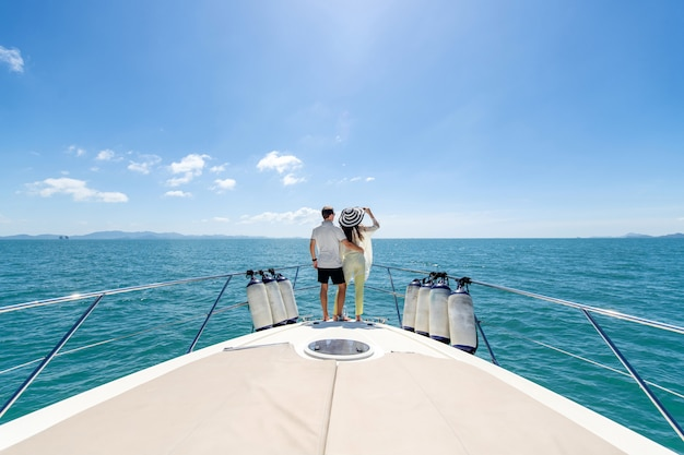 Back view of a sweet couple standing on edge of luxury yacht ...