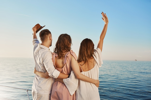 Back view of three best friends travelling by boat hugging and waving while looking at sea. people who are on luxury vacation say hi to ship crue that passes by yacht. Free Photo