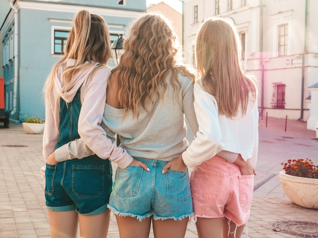 Back view of three young female hipster friends.girls dressed in summer casual clothes.women standing outdoors.they put their hands in shorts in back pockets.posing at sunset Free Photo