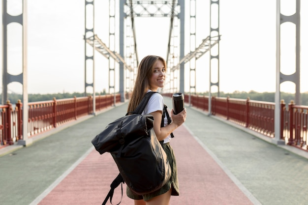 Vista posteriore della donna in viaggio con zaino tenendo il thermos durante il viaggio Foto Gratuite