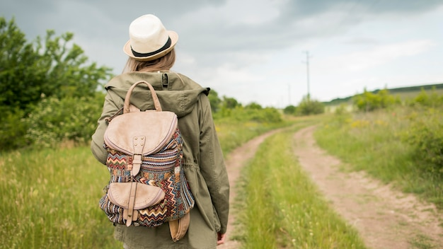 Back view traveller with hat walking outdoors Free Photo