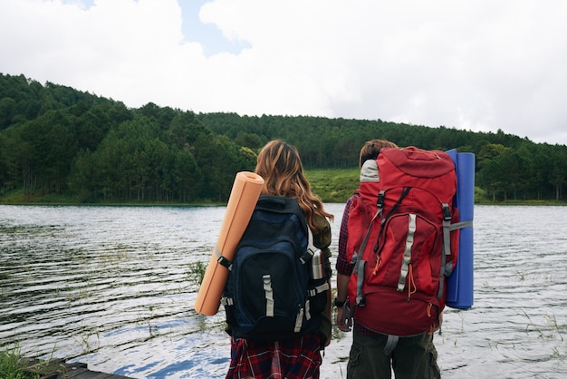 Back view of two hikers with backpacks facing water Free Photo