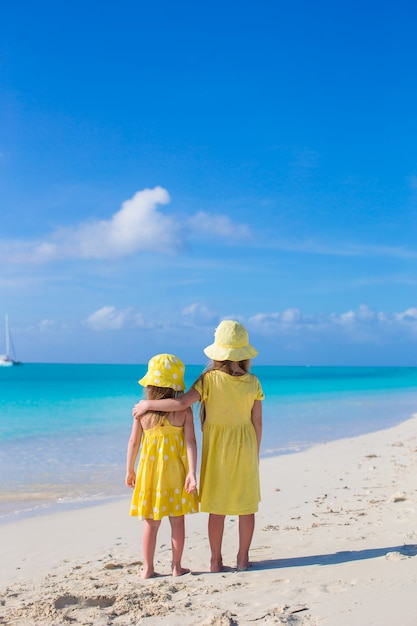 Back view of two little cute girls looking at the sea on white beach Premium Photo