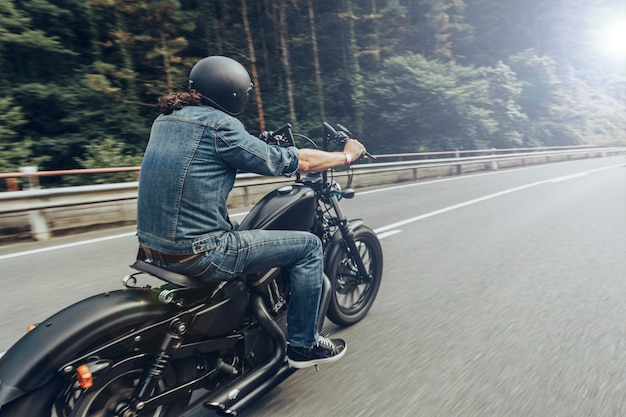Back view of unknown chopper rider along a road across the mountains Premium Photo