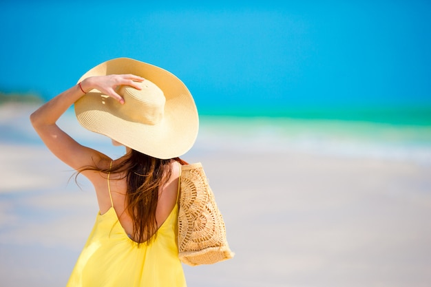 Back view of woman in big hat during tropical beach vacation Premium Photo