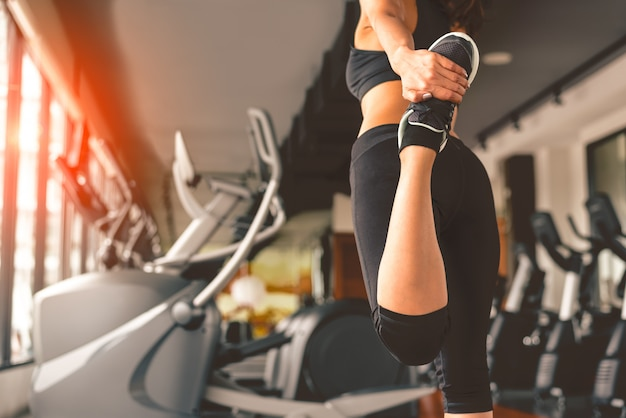 Back view of woman doing yoga in fitness sport training club with sport equipment Premium Photo