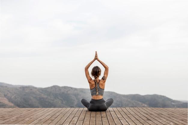 Vista posteriore della donna che fa yoga all'aperto Foto Gratuite