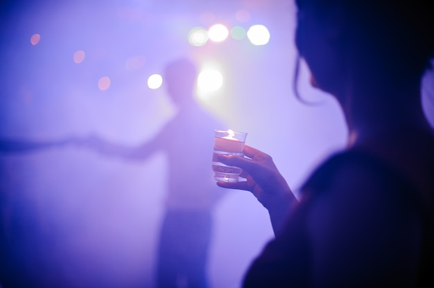 Back view of woman drinking shot in night club Premium Photo