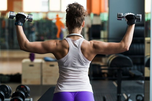 Back view woman exercising with dumbbells Free Photo