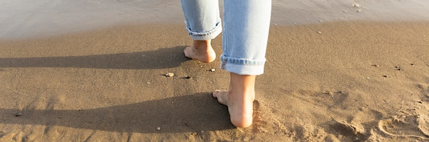 Back view of woman feet on sands Free Photo