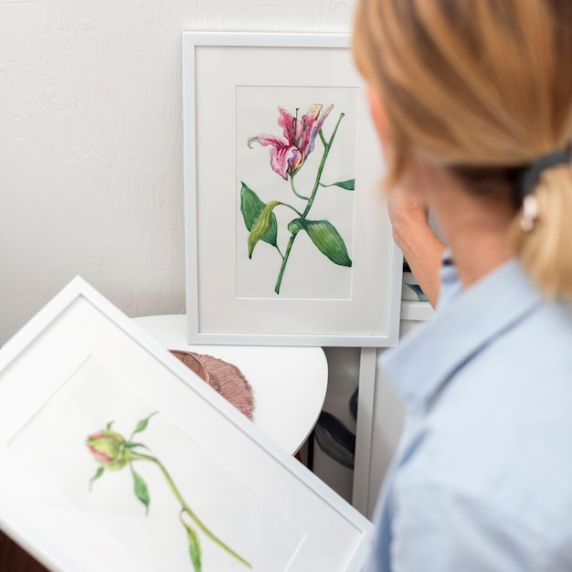 Back view of woman holding flower painting Free Photo