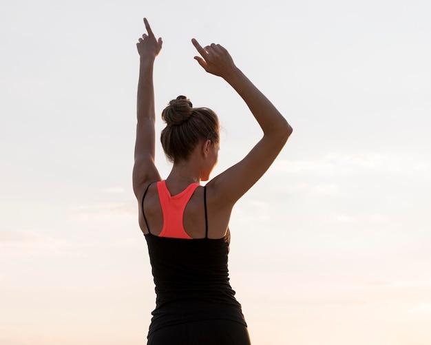 Вид сзади женщина, держащая руки вверх Premium Фотографии
