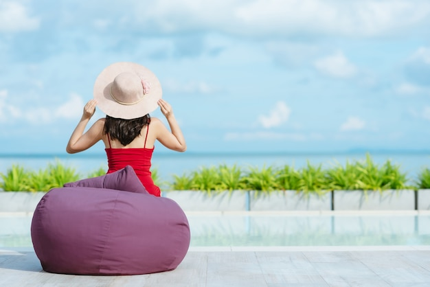 Back view of woman holding straw hat relaxing by swimming pool Premium Photo