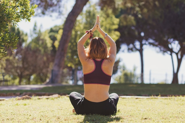 Back view woman meditating in park Free Photo