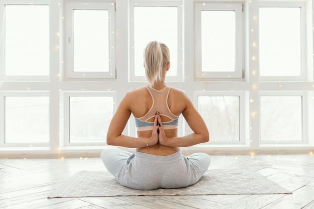 Вид сзади женщина на коврике медитирует Бесплатные Фотографии