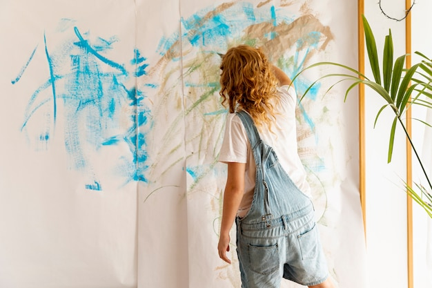 Back view woman painting on the wall Free Photo