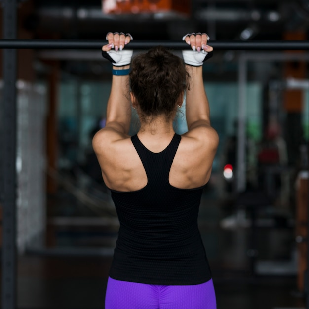 Back view woman performing pull-ups Free Photo