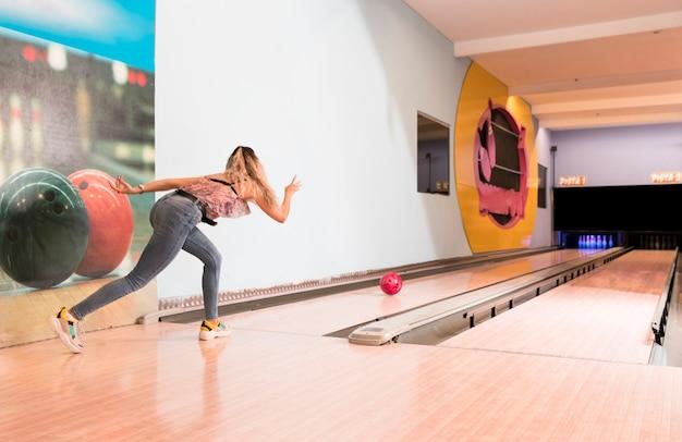 Back view woman playing bowling Free Photo