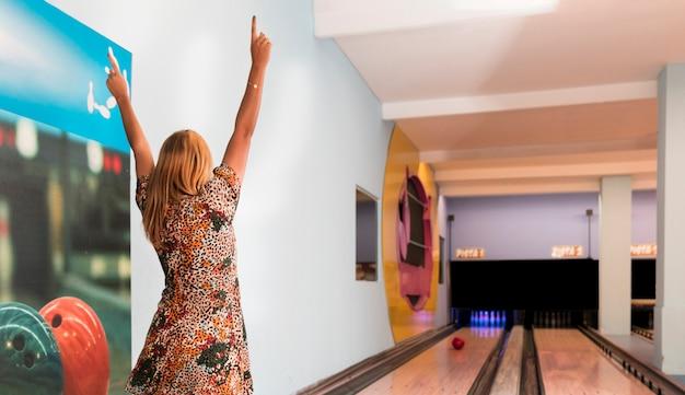 Vista posteriore donna che gioca a bowling Foto Gratuite