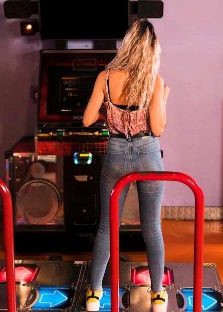 Back view woman playing dancing arcade Free Photo