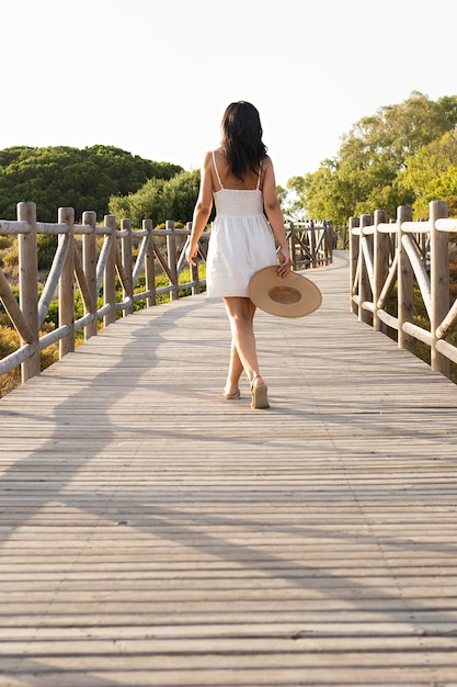 Back view of woman posing on bridge in nature Free Photo