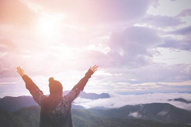 Back view of woman put hands up on landscape in morning. Premium Photo