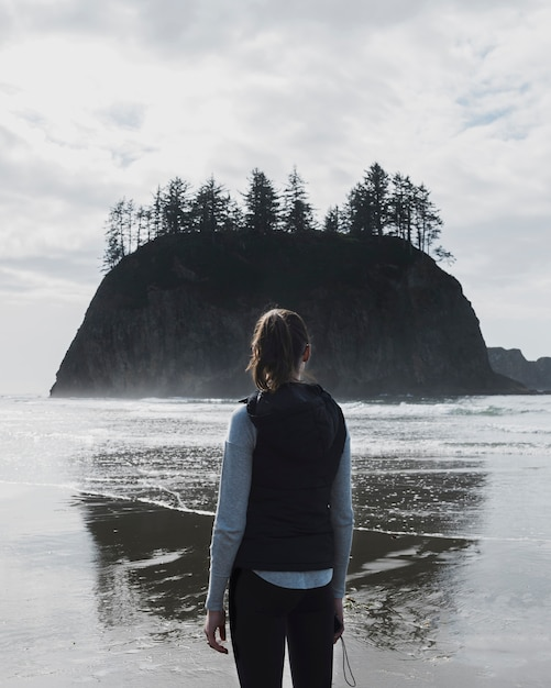 Back view of woman on shore with cliff Free Photo