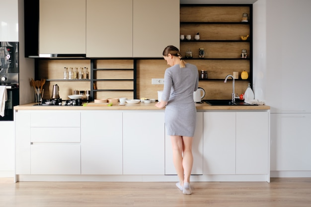 Back view of woman standing next to a modern kitchen Free Photo