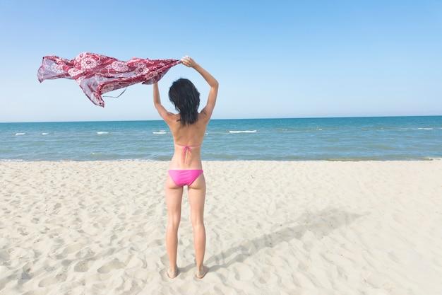 Вид сзади женщина, стоящая на пляже, глядя на море Бесплатные Фотографии