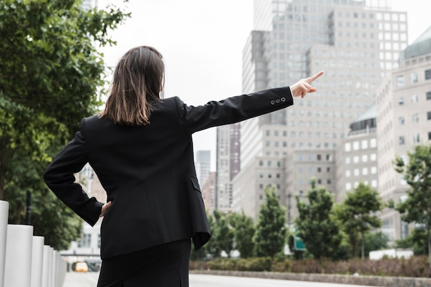 Back view woman in suit pointing up Free Photo